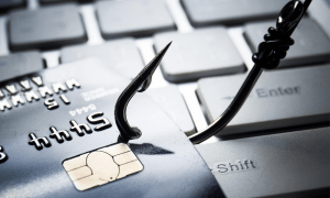 Phishing Scam with hook going through a credit card on top of a keyboard.